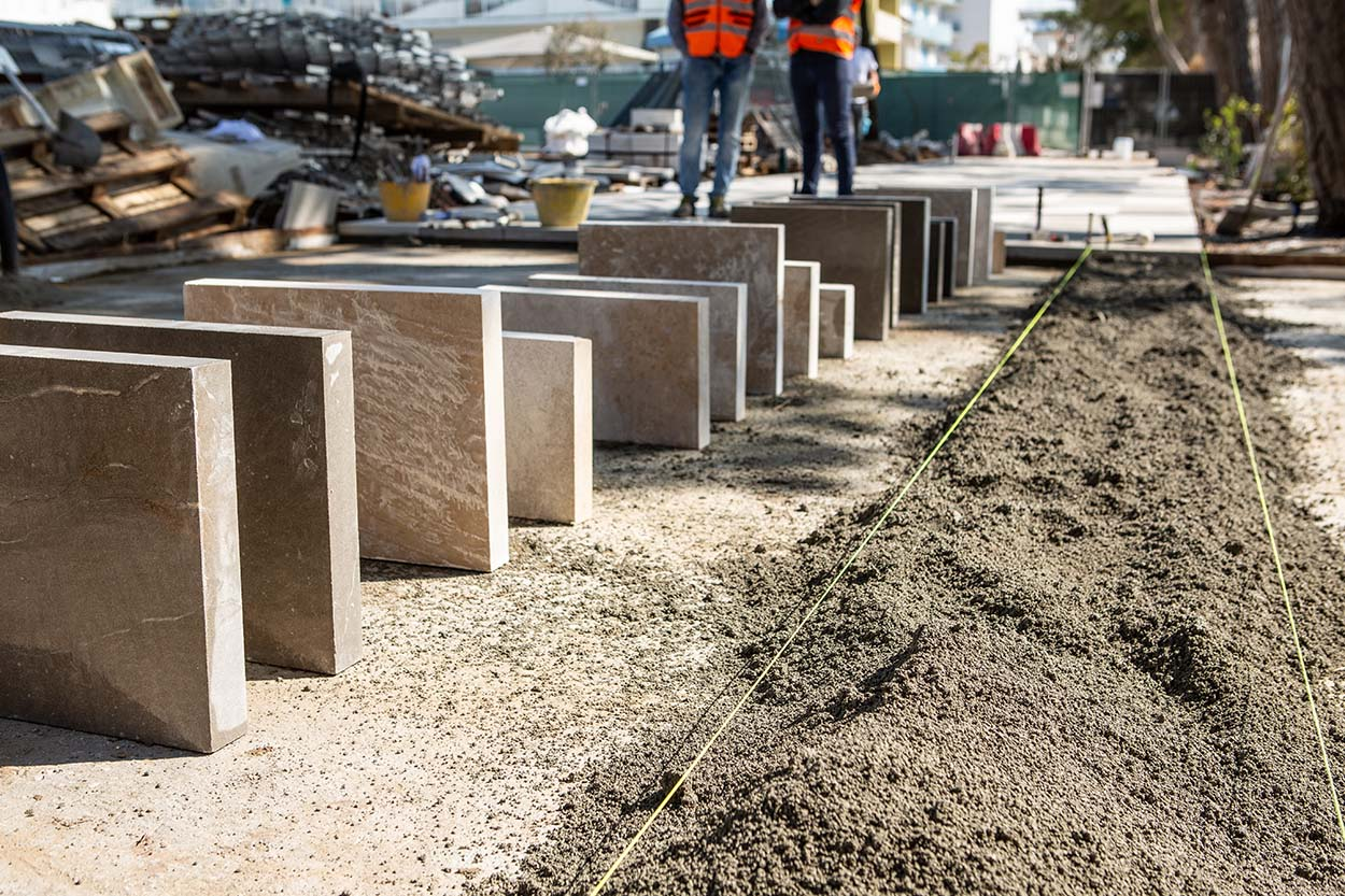 Bedding made of MAPESTONE TFB CUBE pre-mixed mortar and carefully selected stones to be placed along the paving by the flower beds.