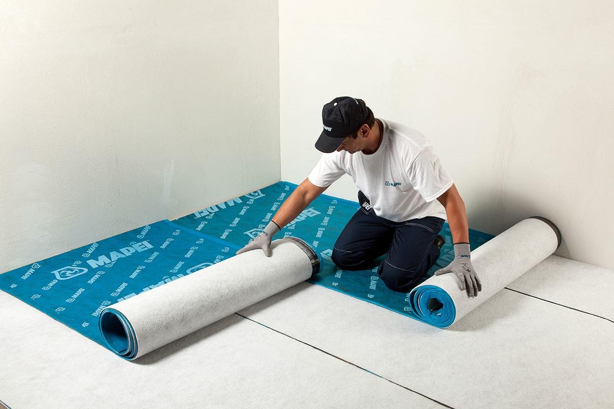 preparazione e posizionamento dell'insonorizzazione in teli sovrapposti di Mapesilent Roll di Mapei